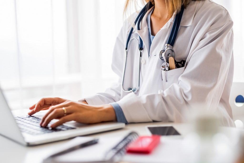 doctor typing on laptop - medical transcription